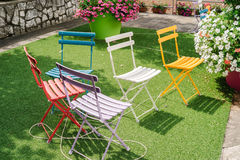 Colored garden chairs. On green grass outdoors Royalty Free Stock Photo