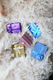 Colored gift boxes scattered on the soft bright plaid fur Royalty Free Stock Image