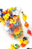 Colored glass beads. In small glass. Isolated comosition Royalty Free Stock Photo