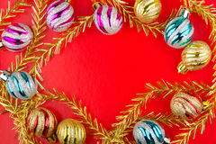 Colored glass Christmas balls and tinsel on red Royalty Free Stock Image