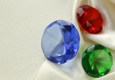 Colored glass diamonds on a soft silk Stock Images