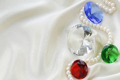 Colored glass diamonds on a soft silk Royalty Free Stock Image