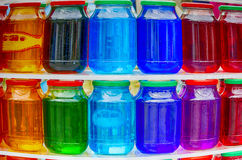 Colored glass jars. Stand in a row Stock Photos