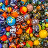 Colored glass marble multicultural community concept. Colored Glass marbles of different sizes in a color pattern as methaphor for multicultural community Royalty Free Stock Photo