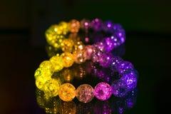 Colored glass marbles , infinity symbol on dark background. Colored glass marbles , infinity symbol on dark stock photos