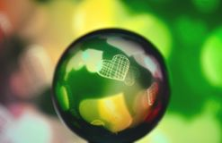 Colored glass sphere with heart. A colored glass sphere with a heart inside in yellow and green tones Royalty Free Stock Photos