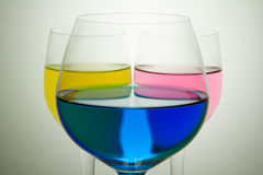 Colored Glasses cyan, magenta and yellow. Three glasses with colored liquid cyan, magenta and yellow Stock Photos