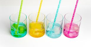 Cold, clean water in rainbow colored glasses. Colored glasses in a row with colored ice and drinking straws filled with cold, fresh water stock photography