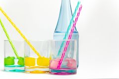 Cold, clean water in rainbow colored glasses. Colored glasses in a row with colored ice and drinking straws filled with cold, fresh water stock images