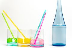 Cold, clean water in rainbow colored glasses. Colored glasses in a row with colored ice and drinking straws filled with cold, fresh water royalty free stock images