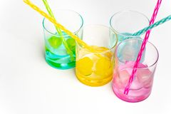Cold, clean water in rainbow colored glasses. Colored glasses in a row with colored ice and drinking straws filled with cold, fresh water royalty free stock photography
