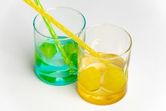 Cold, clean water in rainbow colored glasses. Colored glasses in a row with colored ice and drinking straws filled with cold, fresh water royalty free stock photo