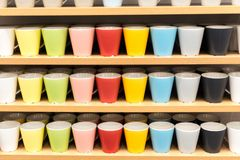 Colored glasses on the shelves in the store. ups of all colors of the rainbow on the counter of the store