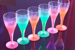Colored glasses are on the table made ​​of black glass. Royalty Free Stock Photo