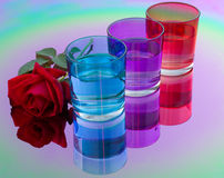 Colored glasses of water. Are reflected in the color table mirror Royalty Free Stock Images