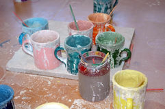 Colored glaze. Mugs with colored glaze, brushes royalty free stock photography