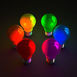 Colored glowing light bulbs standing on dark Royalty Free Stock Photos