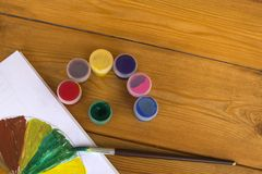 Colored gouache cans on wooden background, Paint for drawing. Kindergarten and school. Multi-colored paint. Children`s stock photo