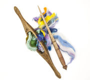 Colored hair and old spindle close-up on white background. Tools for knitting of wool Stock Images