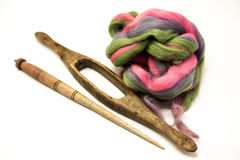 Colored hair and old spindle close-up on white background. Tools for knitting of wool Stock Photos