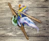 Colored hair and old spindle close-up on wooden background. Tools for knitting of wool Stock Image