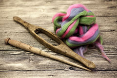 Colored hair and old spindle close-up on wooden background. Tools for knitting of wool Stock Photos