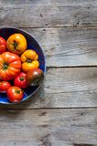Colored halved plate of imperfect tomatoes over old wooden table. Colored halved plate of imperfect red and yellow tomatoes for organic vegetarian menu over royalty free stock photos