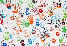 Colored hand prints. On white wall royalty free stock photo