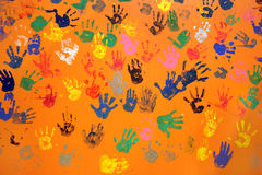 Colored hand prints on orange wall Stock Images