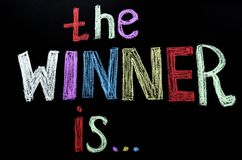 Colored hand written text `the winner is ` on chalkboard.  vector illustration