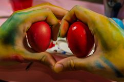 Colored hands making a heart with easter eggs royalty free stock photo
