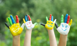 Colored hands with smile painted in colorful paints. Against green summer background. Lifestyle concept stock photography