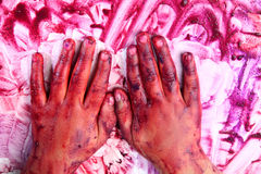 Colored hands. Wet coloured hands of a child in a messy background Royalty Free Stock Image