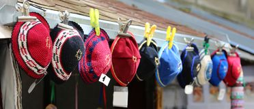 Colored hats typical of Jews called kippahs. Hats typical of Jews embroidered with wool for sale at a stall called kippahs Stock Photo