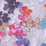Colored hearts scattered on patterned background Royalty Free Stock Photos