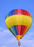 Colored hot-air ballon. A colored hot-air ballon in front of a shiny blue sky royalty free stock image