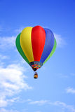 Colored hot-air ballon. A colored hot-air ballon in front of a shiny, light cloudy blue sky royalty free stock photos