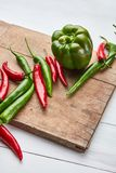 Colored hot chili peppers on a wooden board royalty free stock images