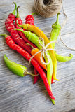 Colored hot chilli peppers on wooden textured background Stock Image