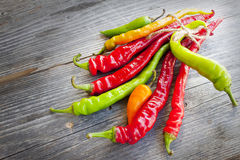 Colored hot chilli peppers on wooden textured background Stock Photo