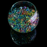 Colored hydrogel balls in a glass vase on a black background stock images