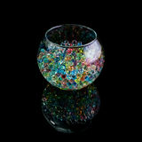 Colored hydrogel balls in a glass vase on a black background royalty free stock photo
