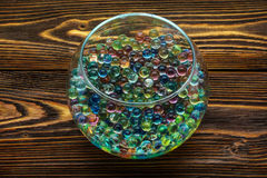 Colored hydrogel balls in a glass vase on old wooden table. Colored hydrogel balls in a glass vase on a wooden table royalty free stock image