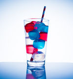 Colored Ice Cubes. Blue and red colored ice cubes in a glass of water Royalty Free Stock Photos