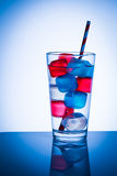 Colored Ice Cubes. Blue and red colored ice cubes in a glass of water Stock Photos