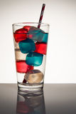 Colored Ice Cubes. Blue and red colored ice cubes in a glass of water Royalty Free Stock Images