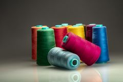Colored industrial spools arranged on dark backgroud royalty free stock image