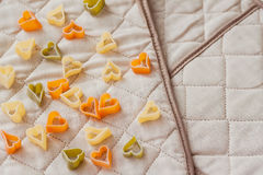 Colored Italian pasta in hearts shape on the kitchen textiles. Food background. Assortment of colorful macaroni Royalty Free Stock Photos