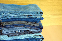 Colored jeans on cupboard shelf, front view close-up Stock Photography