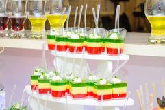 Colored jelly. Colored desserts. Wedding. Colored desserts in glasses. Pieces of cake. Fruit on plates. Candy Bar stock photo